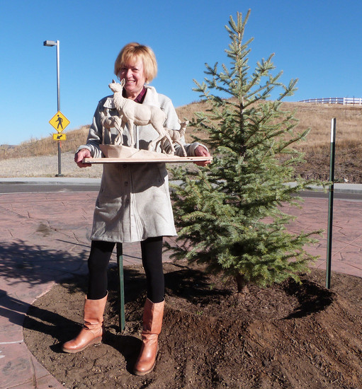 Sculptor Christine Knapp holds up a maquette — a small clay model — on the roundabout at Kimball Avenue and Heritage Road where her sculpture, titled Protecting the Future, of a mother elk and two calves is proposed to go.