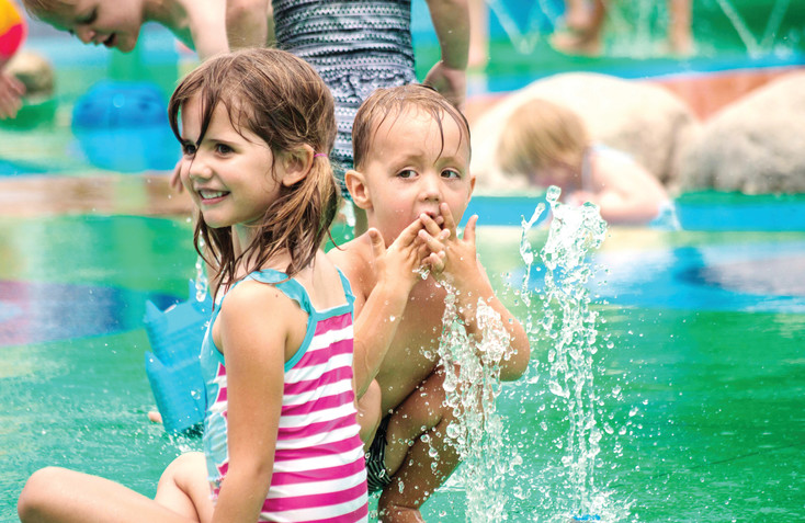 Some of the features of Centennial Center Park's splash pad include a shallow stream running through, fountains and tipping buckets.