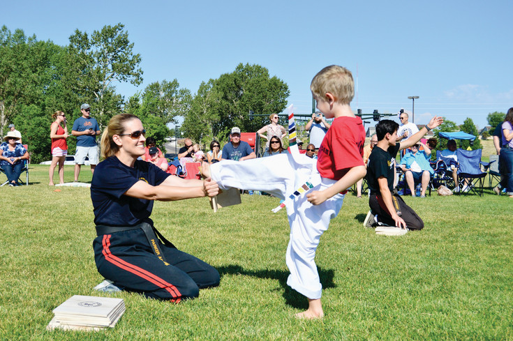 Eli Davidson, a student at the Parker Academy of Martial Arts, kicks through a board held by instructor Lanette Seifert during the annual PAMA in the Park event on July 8. Approximately 300 people came to Hidden River Park to watch students test for their yellow, orange, black and other belts during the event.