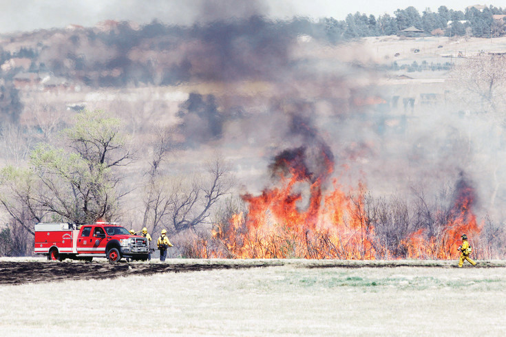 Firefighters with South Metro Fire Rescue burn brush and dried vegetation to control a brushfire near the Challenger Park neighborhood in Parker in April.