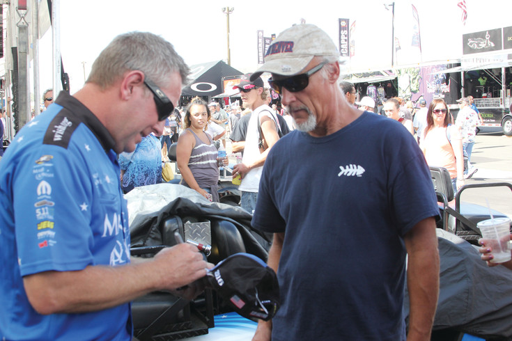 Tommy Johnson Jr., a former area resident and driver of the Make-A-Wish top fuel funny car, signs an autograph for a fan at last year's Mile High National Drag Races at Bandimere Speedway in Morrison.