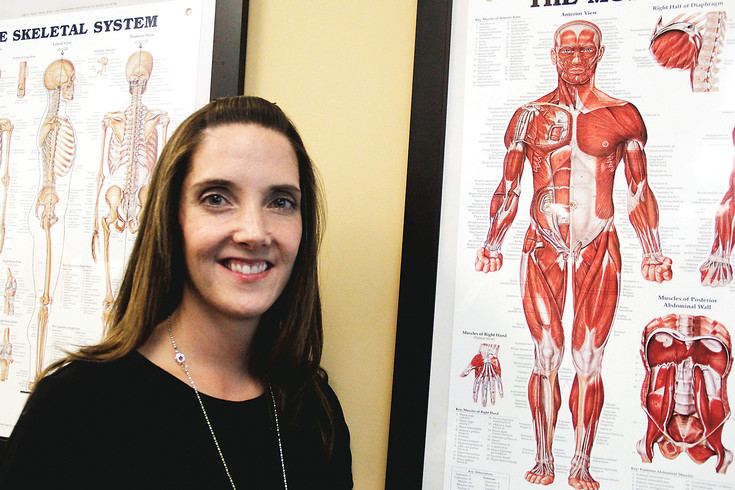 Samantha Hovel, clinic director at Rocky Mountain Spine and Sport in Littleton, poses next to anatomical charts at the center. Hovel uses dry needling as part of a program involving exercise, massage and other techniques to help her patients experiencing muscle spasms, tendonitis and other muscular conditions.