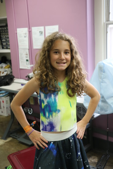 Caroline Ortman, a 10-year-old from Denver, shows off the outfit she made during the Athena Project's fashion design summer camp out of material she picked out on a family vacation to New York City.
