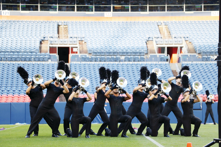 The Columbians, of Washington, strike a pose at the 54th annual Drums Along the Rockies marching music event at Sports Authority Field at Mile High. The marching band kicked off the July 15 event, which featured 10 drum and bugle corps from across the country.