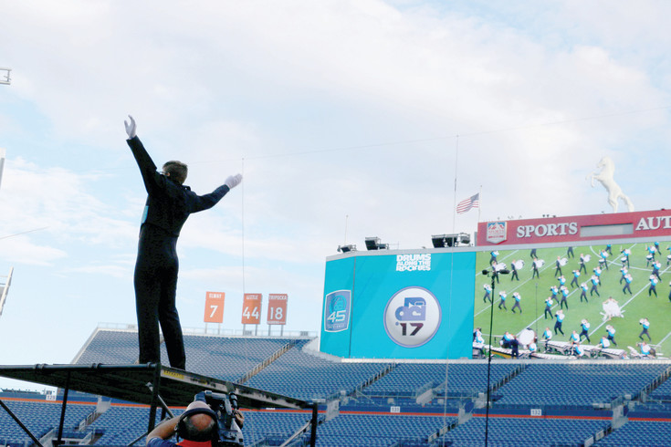 Conductor of the Columbians, a drum and bugle corps from Washington, leads his group from an elevated stand at Sports Authority Field at Mile High at the 54th Drums Along the Rockies. The July 15 marching music event drew thousands of musicians and spectators from across the country.