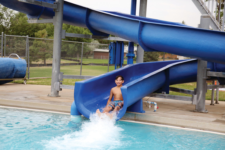 Adrian Fonseca slides down the water slide at Secrest Pool July 12.