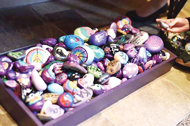 Painted rocks on display at the June 23 memorial service for Katerina Graham, who died May 7 following a suicide attempt that had left her in a coma. Her family and godmother brought hundreds of rocks to the service so attendees could take them home to leave somewhere else. People who knew Graham — and people who didn't — have painted rocks around the world to raise awareness about suicide. Courtesy photo ​