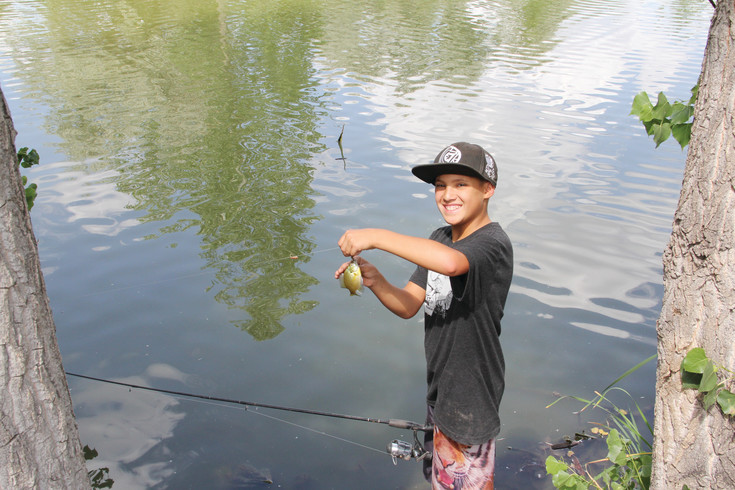 Phoenix Shelton, 12, poses with a fish he caught at the lake in Harvey Park July 13. Shelton, who said he's lived in the neighborhood for two or three years, fishes here during the summer and most of the year, he said. He throws them back once he catches them. Shelton said he sees turtles in the lake, too.