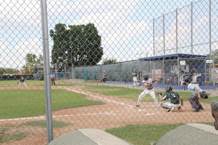 Players from the D'Evelyn Junior/Senior High School Jaguars, from the Jefferson County Public Schools district, play against The Batter's Box club team at Abraham Lincoln High School in Denver July 13. Families watched in the crowd behind the chain-link fence.