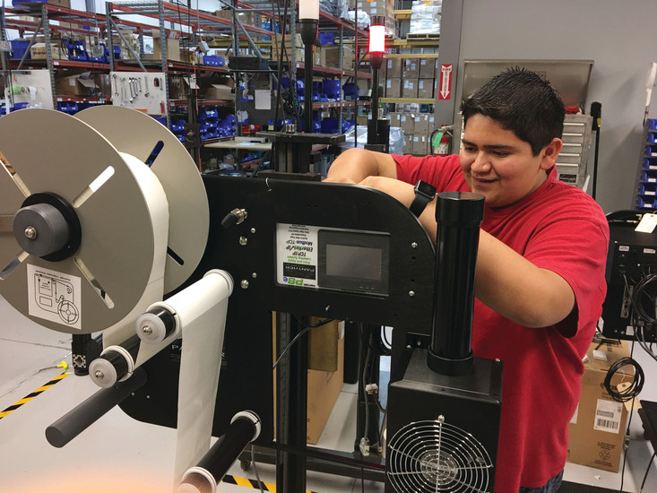 Kendrick Castillo, 16, works on a label printing product at Panther Industries, 8990 Barrons Blvd. Castillo is one of three STEM School and Academy students involved in the company's first intern program this summer that lasts eight weeks.