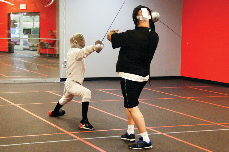 "Brendan Barber, 13, lunges at coach Elliott Clinton during a training session at the Fencing Academy of Parker on July 13. Clinton says fencing is often referred to as ""physical chess' because it requires strategy, outsmarting an opponent and thinking ahead."