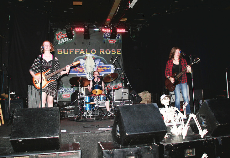 The Skeleton Dolls of Golden, from left Cadence Fisher, 15, on bass, Aria Fisher, 12, on drums and Harmony Fisher, 17, on guitar perform at Golden Summer Jam on July 14 at the Buffalo Rose in Golden.