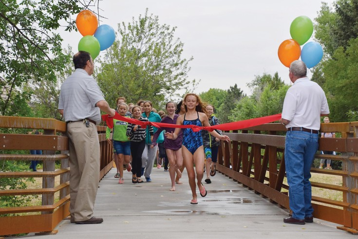 Members of the Franklin Fish swim team from South Suburban's Franklin Pool inaugurate the new Franklin Street Bridge after swim practice. On June 30, South Suburban and project partners celebrated the completion of the High Line Canal Bridge Replacement Project and the new bridge.
