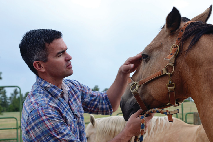 Chase Kohne examines a horse at a ranch near Castle Rock on July 8. Kohne, a Democrat and major in the United States Army, recently announced his campaign to unseat Republican Ken Buck in Colorado's 4th Congressional District.