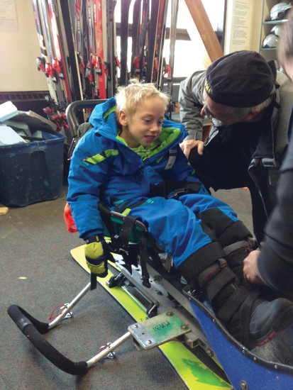 Ezekiel Coles is fitted into specialty equipment used to help people with disabilities participate in recreational sports.