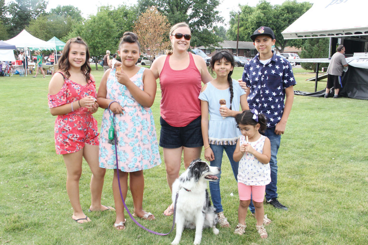 Karen Johnson, 39, stands with her dog, Dakota, at the Harvey Park Improvement Association Summer Festival July 22. She stood with, from left to right, Leilani Ortega, 14; Presais Ortega, 12; Bella Lucero, 11; Olivia Lucero, 2; and Adrian Ortega, 13. Johnson's business, Suncrest Hospice, had a booth at the festival, she said.
