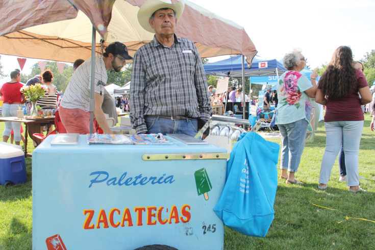 Rafael Diaz, 77, poses with his cart of popsicles at the Harvey Park summer festival July 22. He walked around ringing bells on the cart to signal to customers.
