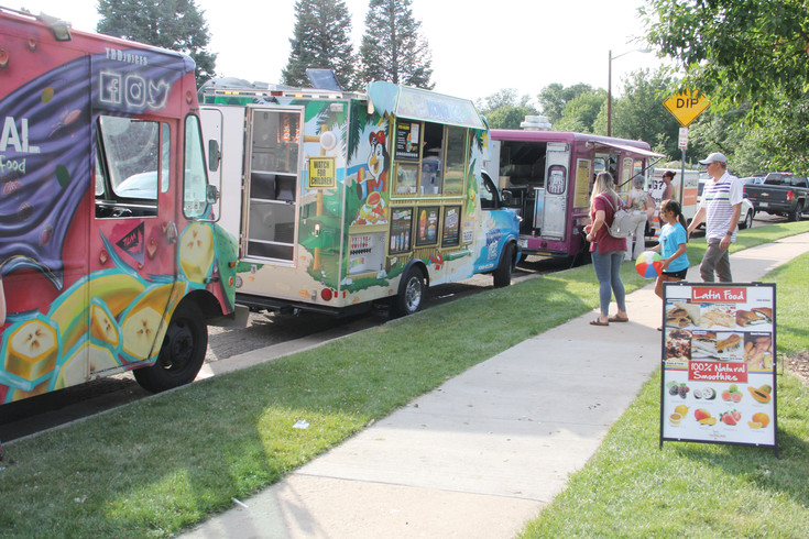 From left to right, The Real Deal, Kona Ice and Hey PB&J food trucks parked along the Harvey Park summer festival July 22. A food truck in the form of a trailer sat, not pictured, to the left: Pavy's Sandwiches.
