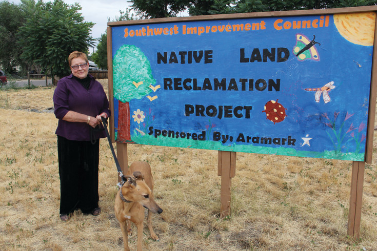 "Jan Marie Belle, executive director of the Southwest Improvement Council nonprofit in the Westwood neighborhood of Denver, stands with her greyhound Rexie July 20 on a plot of land SWIC owns — a community garden sits on the land just steps away. Belle stood on the part of the land that SWIC remade into what it calls a ""native land reclamation project"" — an effort to maintain the land as a space that plants and wildlife can survive or spend time on."