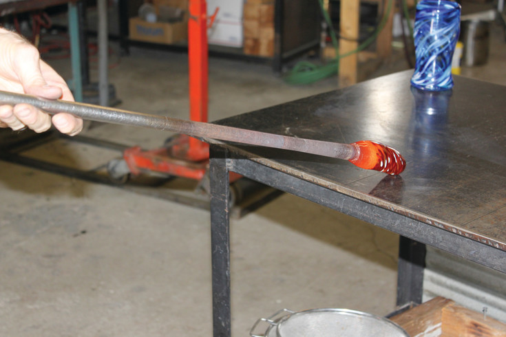 Artist Corey Silverman works a piece of red hot glass in the foreground, which will eventually become a blue swirled glass like the one in the background.