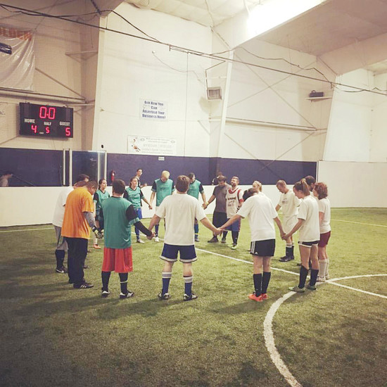 Team members and opponents gather together to pray before a soccer game at Red Rocks Church's sports ministry tournament.