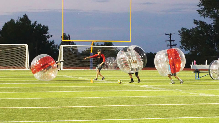 Participants in bubble soccer run after the ball for a fun game in Red Rocks Church sports ministry's sport tournament.