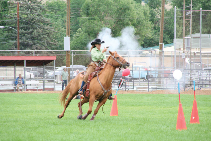 A rider with the Colorado Regulators — a mounted shooting club — wows the crowd with her shooting skills during Monarch Productions' Cody's Wild West show on July 29.