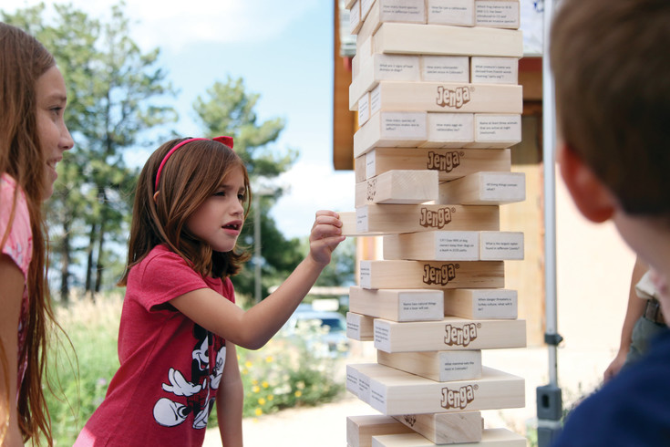 Mila Ojeda plays nature trivia Jenga with her siblings at the Boettcher Mansion 100 year celebration.
