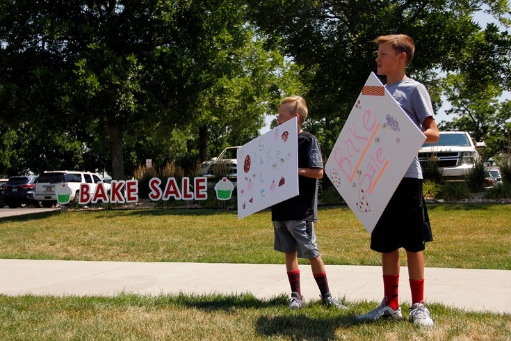 "Josh Nelson, 12, left, and Tyler Sreenen, 12, advertise the bake sale to raise money for Colton Love's medical expenses. Nelson, a classmate of Love's, describes him as ""such a silly person."" Photo by Tom Skelley."