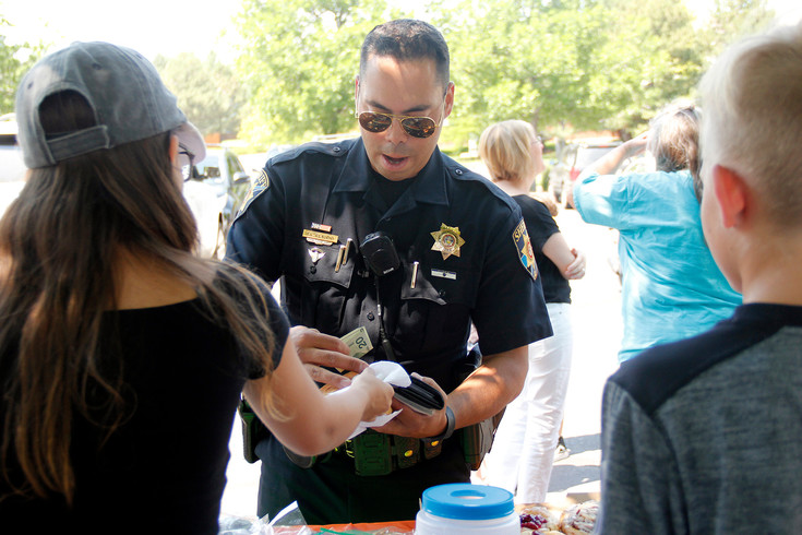 Douglas County Sheriff's Deputy Felix Claudio buys some baked goods after checking in with the Love family. Claudio led the investigation into the hit-and-run, and said the entire department has been monitoring Colton Love's recovery. Photo by Tom Skelley.