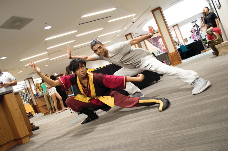 "Leila Browne and Kish Stars hold a fire bending pose relating to Browne's character of Zuko from ""Avatar: The Last Airbender"" at Koelbel Con at the Koelbel Library on July 30."
