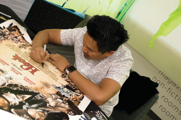 "Actor Dante Basco autographs the movie poster of ""Hook,"" the movie that introduced the actor to the world. Basco was part of a panel of authors and was interviewed at Koelbel Con."