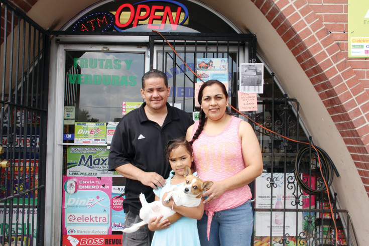 Hector Medina, 44, Maria Medina, 43, and Brianna Medina, 6, stand with their dog Lola in front of the Medinas' small business, Abarrotes Medina's convenience store, July 26. In addition to snacks and foods characteristic of a convenience store, the shop on the 4300 block of Morrison Road also sells traditional Mexican snacks.