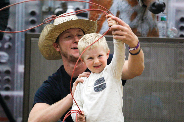 Kasen Jachetta, 4, gets a roping lesson from Zach Wyatt after the Xtreme Bulls rodeo event at the Douglas County Fair and Rodeo on Aug. 3. The fairground arena hosted the competition, accented by a truck giveaway and rodeo royalty from around the United States.