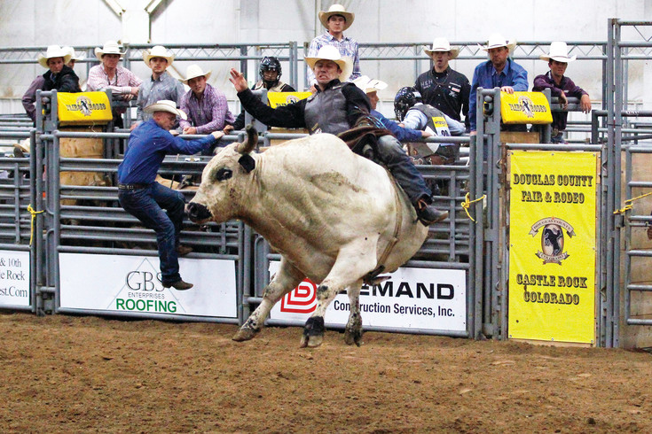 Mike Sparks of Caldwell, Idaho, holds on as his bull, Crophopper takes him for a spin at the Douglas County Fair and Rodeo's Xtreme Bulls event. Thirty-nine cowboys rode in the fast-paced competition.