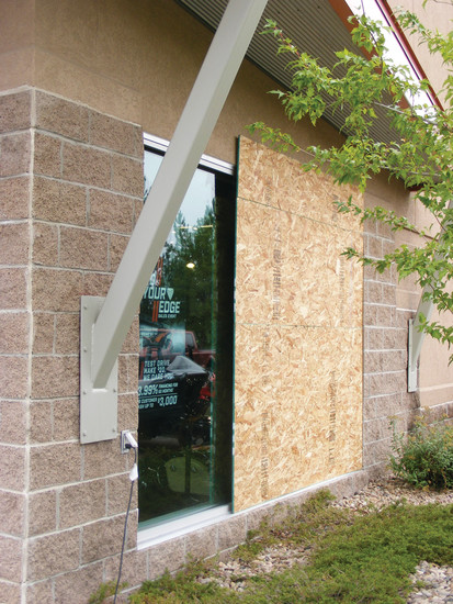 Particle board covers the window thieves smashed to gain access to Warhorse Firearms of the Rockies on July 26.