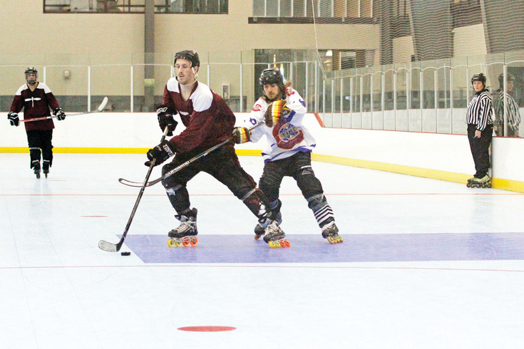 C.J. Piz, left, skates past Mike Dalonski during an inline hockey game as referee Emily Redgate looks on at the Parker Fieldhouse on July 31. Checking is officially prohibited in the league, though physicality is still a part of the game.