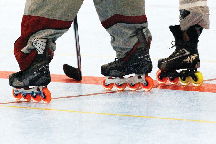 Players' inline skates, more colorful than their icy counterparts, stand poised for the drop of the puck during a face off.