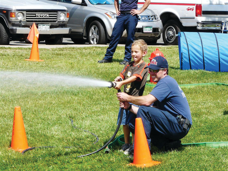 A Westminster firefighter helps steady a child's grip on the firehose at last year's WestyFest. The fire department's Kiddie Combat Course will return to the festival's Adventure Land zone  Aug. 12 in Westminster City Park.