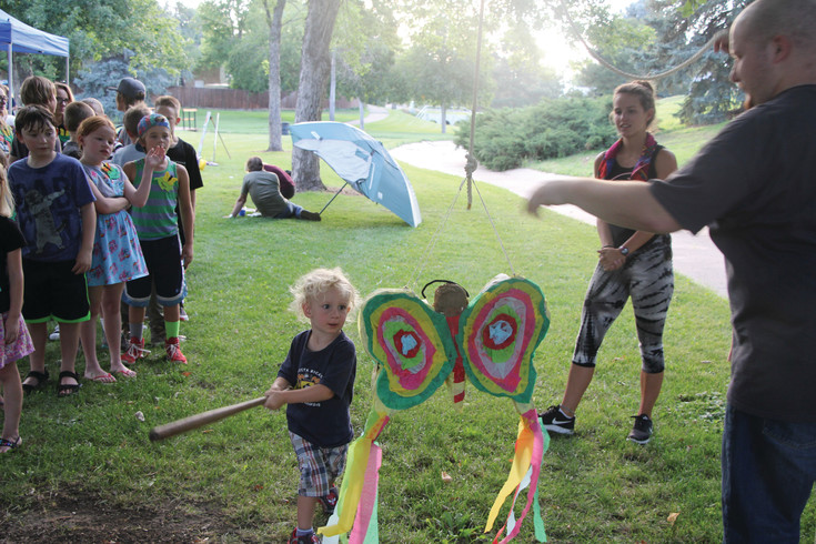 Killian Higham, a 2 ½-year-old, takes the first swing at a piñata during the Aug. 1 National Night Out gathering on the Stanford greenbelt. Organizers invited the residents of three blocks in the area to attend the event as a chance to meet neighbors. There was a pot-luck meal and, while adults ate and chatted, there were activities for children like the piñata and a water balloon fight.
