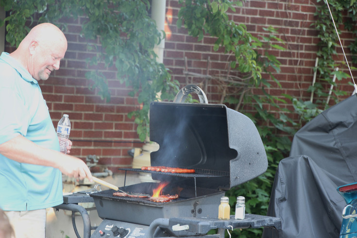 Flames flare up as John Gerlick prepares to flip a burger he is cooking for the guests at the Aug. 1 National Night Out gathering he organized. Gerlick invited 100 neighbors to attend the gathering that is part of a national event focused on getting people to meet and greet their neighbors. There were 32 NNO events in Englewood this year.