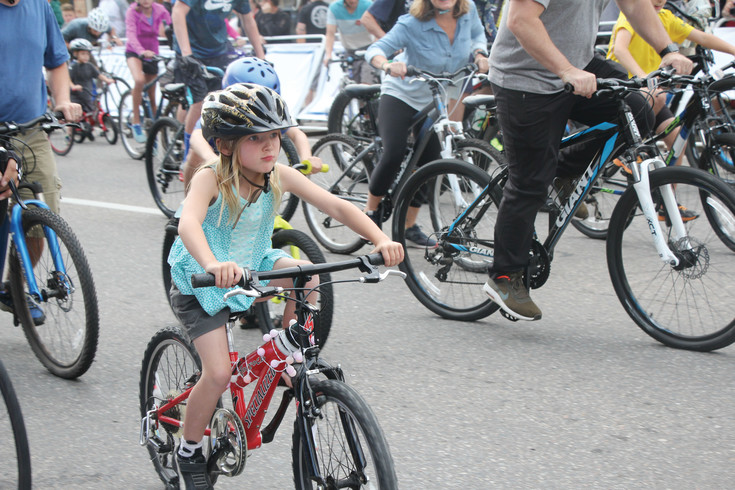 Lily Freitas, 6, pushes off at the start of the cruiser ride that was part of the Aug. 5 Littleton Twilight Criterium. More than 100 adults and children took the opportunity to ride their bikes around the L-shaped course that was set up for the bike racers. There were six events during the criterium and the cruiser ride was the only event that wasn't a race.