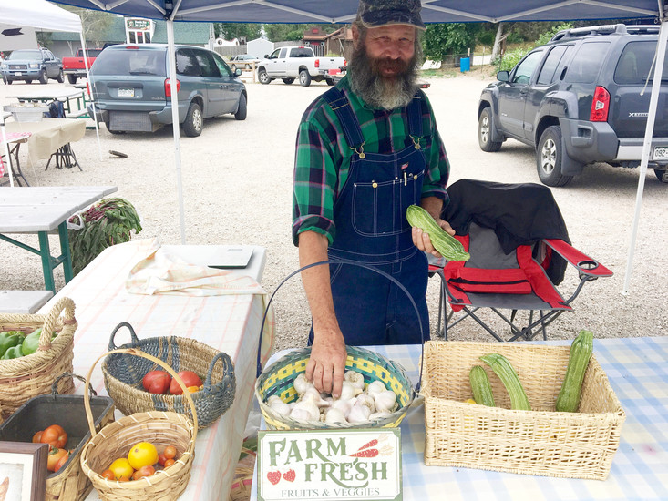 Gardener Greg Caldwell reaches to show off his organically grown garlic and zucchini from his home gardens at the Town of Elizabeth Farmer's Market July 29.