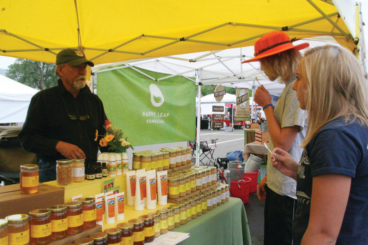 Dave Boudreaux, an employee and beekeeper with Björn's Colorado Honey, left, chats with Colorado Mines students Dallas Frisbie, front, and Trevor Lockman about at the Golden Farmers' Market on June 24. Björn's has been vending at farmers' markets for five years, and this is the second year for family-owned business to attend the Golden Farmers' Market.