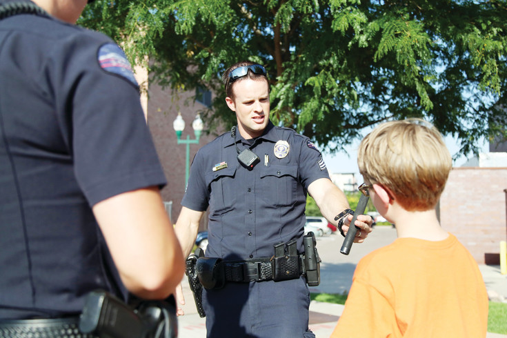 Arvada Police Sgt. Ian Hetrick shows off his gear to an Arvada kid at the National Night Out.