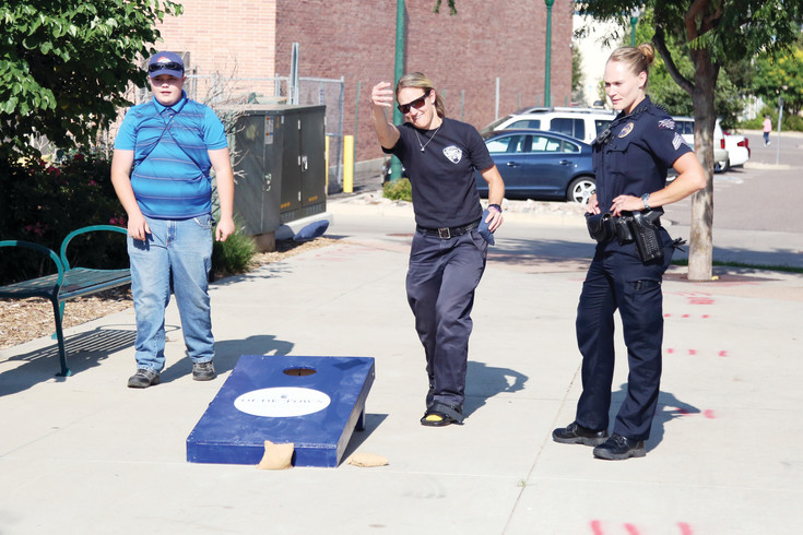 Amber Jones, of Arvada Fire, plays corn hole at the annual celebration.