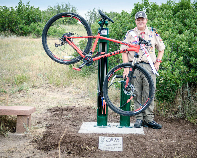 Carter Kavalec, of Boy Scouts Troop 645, stands next to a new Dero Fixit Service Station on Outlaw Trail, west of Griggs Road in the Backcountry Wilderness Area. An avid trail rider, Kavalec installed the station as his Eagle Scout project to help fellow riders.