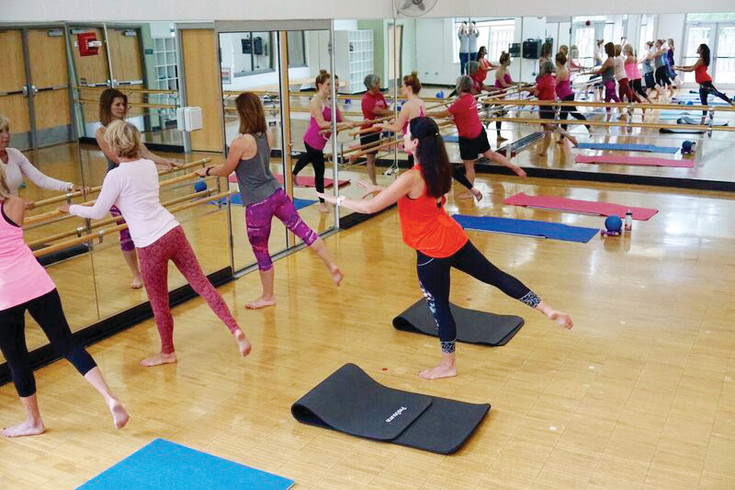 Community members perform small movements using a ballet bar at a Highlands Ranch Community Association barre class. The ballet-inspired workout leans muscles and strengthens core.