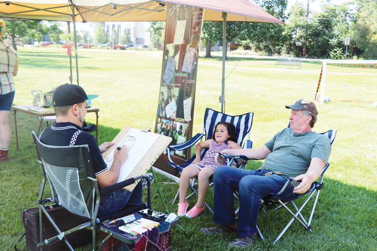 Anabelle and her grandfather Tom Walden  get a caricature drawn by Sean Hyatt of Artsy Events at Wheat Ridge's annual National Night Out celebration on Aug. 1.