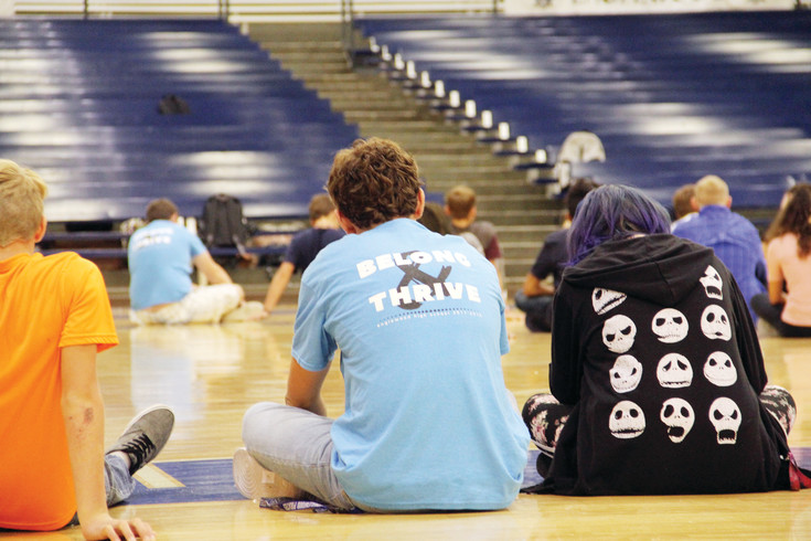 "An upperclassman and member of the Link Crew, student leaders who help introduce new freshman to high school, sits next to freshman students in the gym at Englewood High School on the first day of school Aug. 10. Freshman participated in ice-breaker exercises before breaking into small-group activities with the Link leaders, whose shirts read ""Belong and thrive."""